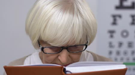 blindness : Sad elderly woman in eyeglasses reading book, vision problems, blindness
