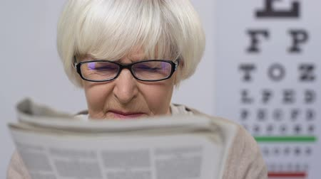 blindness : Upset senior woman in eyeglasses reading newspaper, vision problems, illness