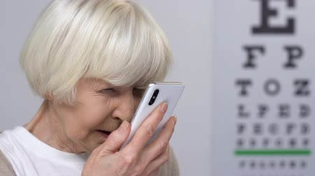 blindness : Senior female with vision problems reading message on smartphone, blindness
