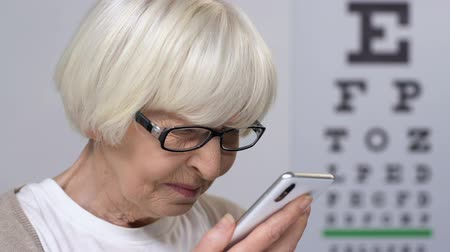 blindness : Aged woman in eyeglasses reading message on smartphone, vision disease