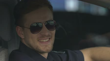 patrolman : Kind policeman in sunglasses smiling for camera sitting in patrol car, close-up