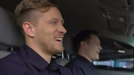 patrolman : Cheerful policemen laughing sitting in patrol car, friendship at work, cops