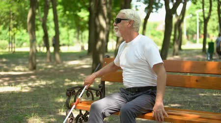 Old blind man finding long cane on bench, walking in park independent, rest Stock Footage