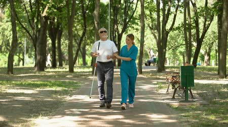 assistência : Young nurse holding blind old patient walking in park, vision restore clinic