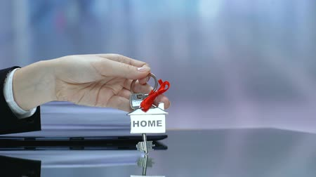 владелец : Female holding key from home with red ribbon, real estate purchase, dream house Стоковые видеозаписи