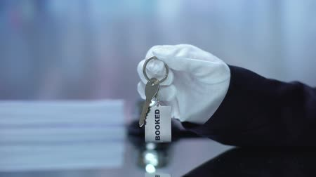 administrador : Receptionist passing booked key chain to client, hotel business, hospitality