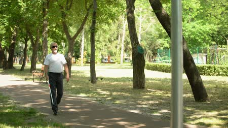 blindness : Blind old man detecting obstacles with white cane, bumping into pillar in park Stock Footage