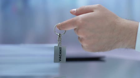 vacant : Vacant word written on keychain female taking from male boss hand, employment Stock Footage