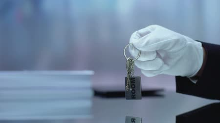 inchecken : Hotel receptionist hand giving customer keys from booked room, hospitality