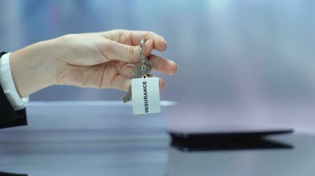 tomar : Insurance written on keychain client taking from desk, property protection, care