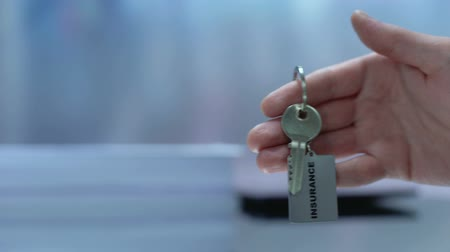 tomar : Female customer taking keychain from insurance agent, health protection, care Stock Footage