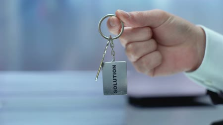 wynalazek : Solution word on keychain hand showing to camera, accepting opportunity, startup