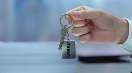 tomar : Dream word on keychain hand showing to camera, key to future, motivation