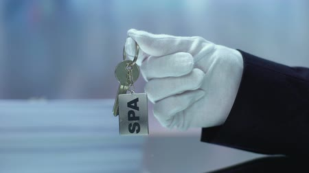 отель : Receptionist in glove shoving to camera SPA keys, five star resort, body care