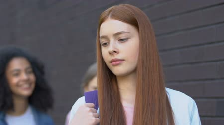 overcome : Teen girl ignoring mockery of classmates, resisting bullying, inner strengths Stock Footage