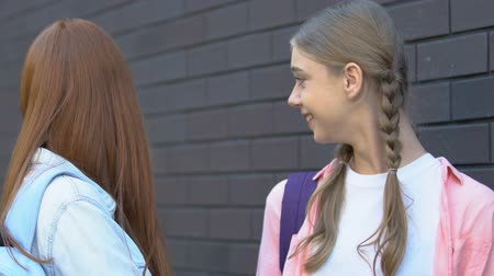 médio : Teenage girls gossiping about classmate passing by, bad rumors, disrespect Stock Footage