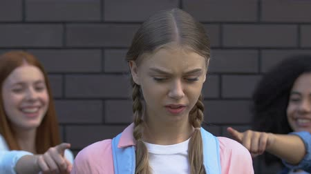 vélemény : Teens pointing fingers at depressed girl, making victim feel guilty, bullying