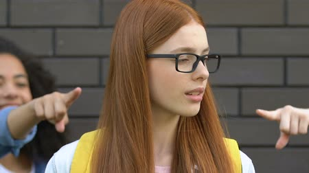 médio : Mean schoolchildren pointing fingers at smart girl, teasing about eyeglasses