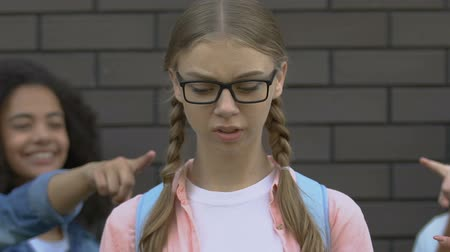 significar : Mean teenagers pointing fingers at girl in eyeglasses, cruelty and hate of peers Stock Footage