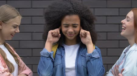vélemény : Biracial teenage girl covering ears from bullying, mockery of classmates, racism Stock mozgókép