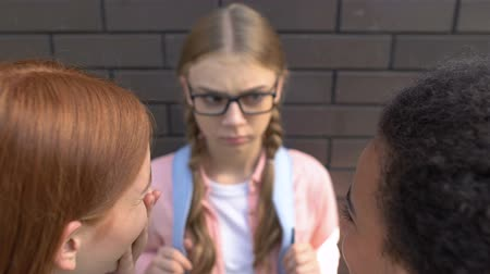 přestupek : Classmates laughing at pretty girl in eyeglasses, malicious teasing, bullying Dostupné videozáznamy