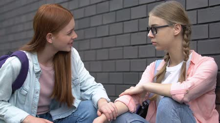 телефон доверия : Female student giving helping hand to bullied nerd girl, supportive friend