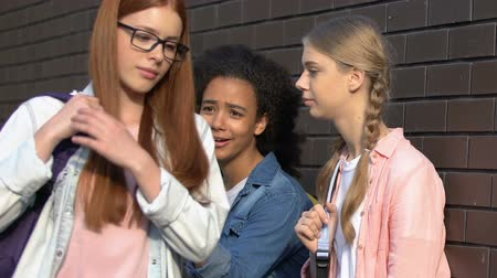 одноклассник : Female teenagers teasing girl in schoolyard, mocking appearance, calling names