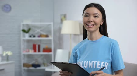 donate : Female volunteer making notes and smiling on camera, to-do list, charity project