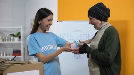 пожертвование : Smiling volunteer presenting gift box to needy aged female, philanthropy care Стоковые видеозаписи