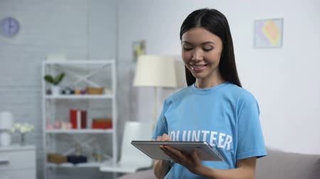 tür : Cheerful volunteer with tablet smiling camera, online fundraising application