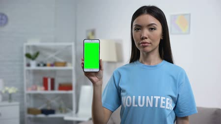 rada : Charity fund worker showing smartphone green screen, volunteering app, help Wideo