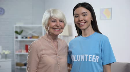 фонд : Happy aged woman and female volunteer smiling on camera, old people support