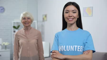 tür : Smiling young volunteer with happy old lady on background, social protection Stok Video