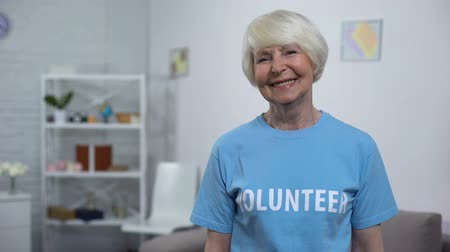 olgun : Smiling senior lady in volunteer t-shirt looking camera, charity organization