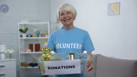 voluntário : Happy female volunteer holding donation box, food for poor people, assistance