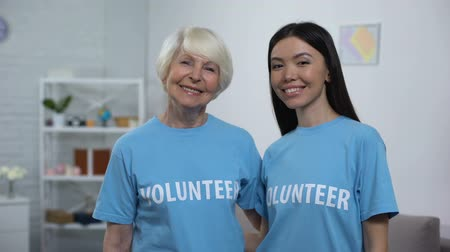tür : Mature and young women in volunteer t-shirts smiling on camera, assistance