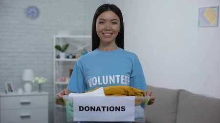 voluntary : Joyful social activist holding donation box with clothes, social volunteering Stock Footage