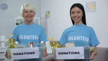 жертва : Smiling senior and young volunteers holding food donation boxes looking camera