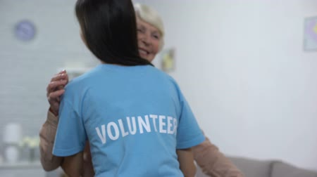 tür : Young female volunteer hugging smiling aged lady, old people care, nursing home Stok Video