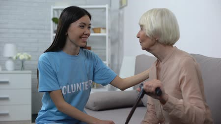 фонд : Smiling female volunteer talking to senior woman with walking stick, attention