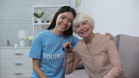 pacjent : Young female volunteer hugging mature pensioner walking stick smiling camera Wideo
