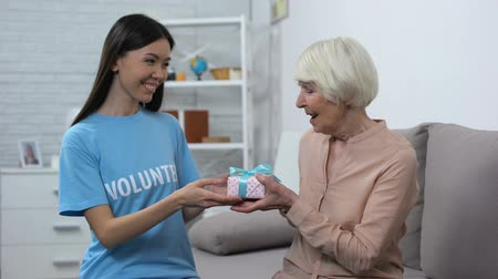 philanthropy : Female social worker giving present smiling aged lady, birthday greeting, care Stock Footage