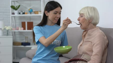 tür : Young volunteer feeding old woman nursing home, taking care of hospice patient