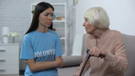 беспокоюсь : Worried senior woman talking to young female volunteer, nursing home support