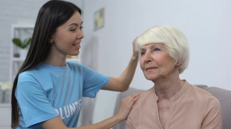tür : Kind volunteer combing aged woman hair, old patient care, smiling each other