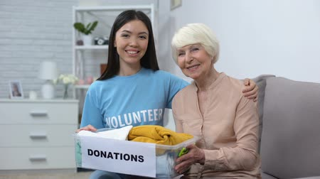 voluntário : Happy female volunteer and aged woman holding donation box, humanitarian aid