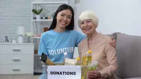voluntary : Caring activist hugging female pensioner holding donation food box, support Stock Footage