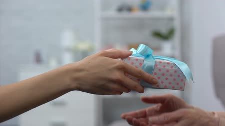 празднование : Female hands giving present box to elderly woman, birthday greeting, family care Стоковые видеозаписи