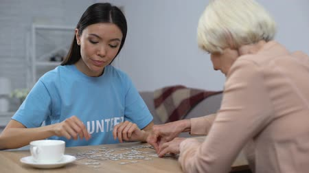 puzle : Young volunteer helping aged woman playing puzzle game in nursing home, care Wideo