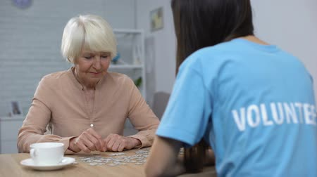 unterstützung : Female pensioner young volunteer putting puzzle together, old people attention
